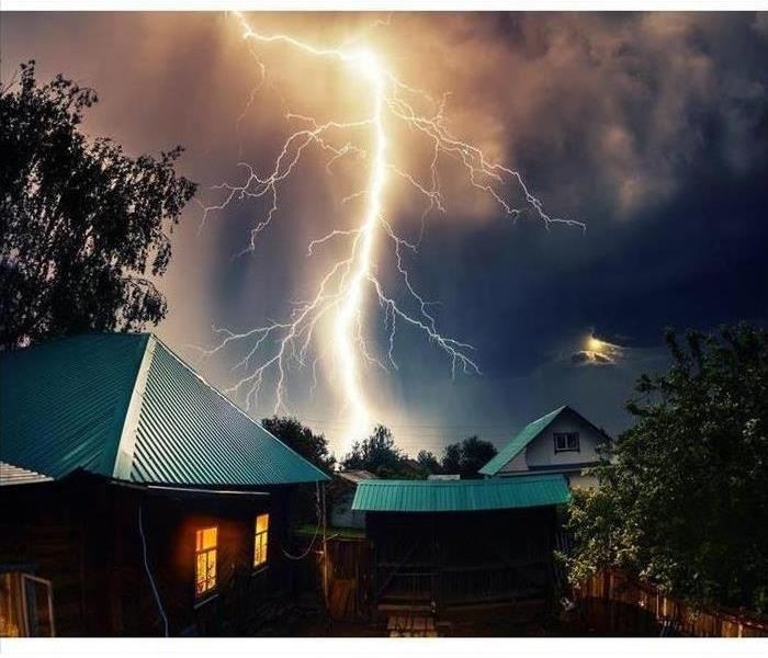 bolt of lightning striking behind two homes
